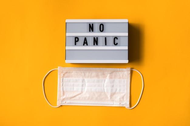 Хирургическая маска с текстом no panic на белом лайтбоксе, изолированном на желтом фоне. остановить вирус. коронавирус пандемия. концепция загрязнения воздуха, плоский баннер