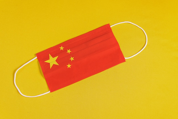 Surgical mask on yellow background with flag of china