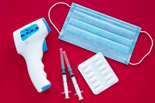ウイルスから保護するための外科用医療マスク、温度を測定するための赤外線額非接触温度計ガン、コロナウイルス(covid-19)テスト。インフルエンザの流行。