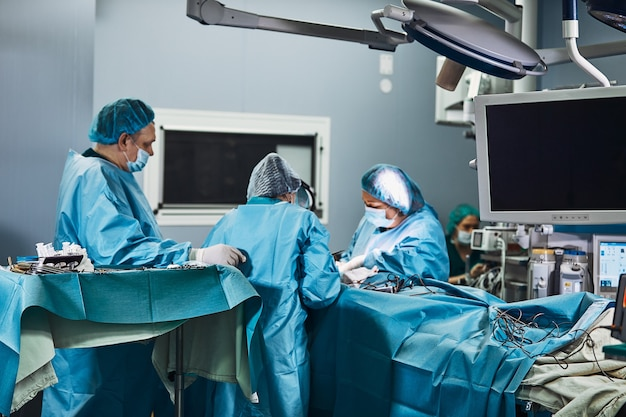 Surgical team operating on patient in theater in hospital.