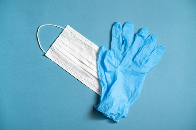 Surgical white mask and latex gloves for protection on a blue