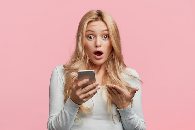 Surpised businesswoman reads unexpected news about startup, checks email on modern cell phone, looks worried as recives message from boss, isolated over pink wall. omg and surprisment concept