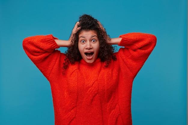 놀란 흥분된 여자는 그녀의 성공을 믿지 않고 손을 머리에 붙입니다.