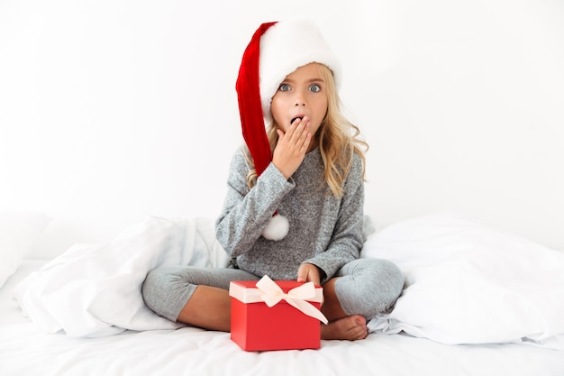 Surpised little girl in santa's hat holding present while sitting with crossed legs in bed