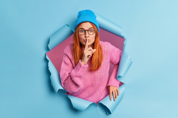 Surpised redhead young woman looks mysteriosly keeps index finger over lips tells secret information gossips about something wears hat and pink sweater.