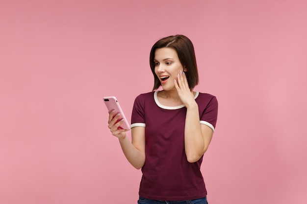 Surpised young brunette woman holding pink smartphone,