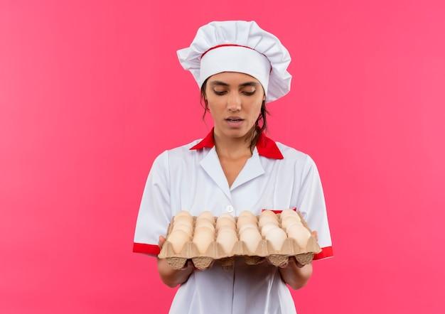 コピースペースで卵のバッチを保持し、見ているシェフの制服を着て驚いた若い女性料理人