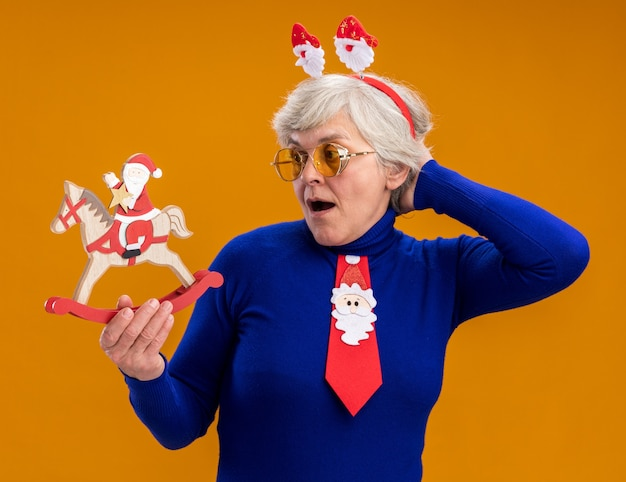 Surpried elderly woman in sun glasses with santa headband and santa tie holding and looking at santa on rocking horse decoration isolated on orange background with copy space