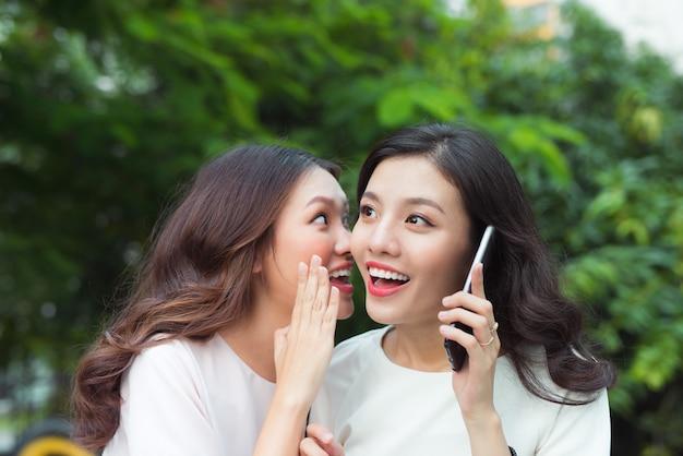 전화하는 동안 쾌활한 친구에게 속삭이는 놀란 젊은 여자