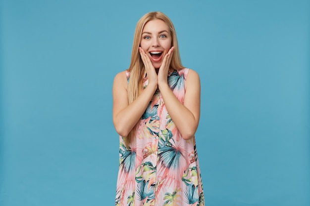 서서 그녀의 뺨에 손을 잡고 놀란 찾고 꽃 드레스에 서프라이즈 젊은 긴 머리 금발 아가씨