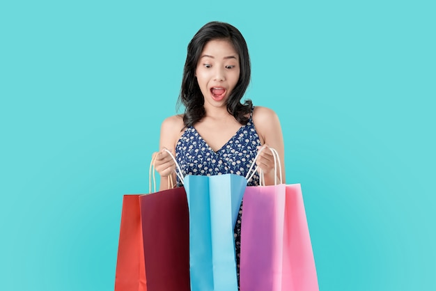Surprise asian woman for gift in the shopping bags on light blue.