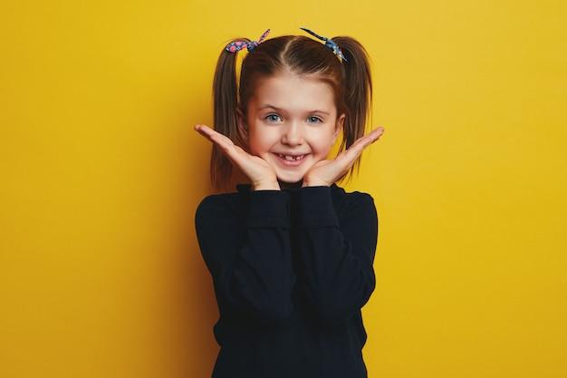 Удивленная удивленная милая девочка-подросток раскрывает ладони и показывает свое привлекательное личико