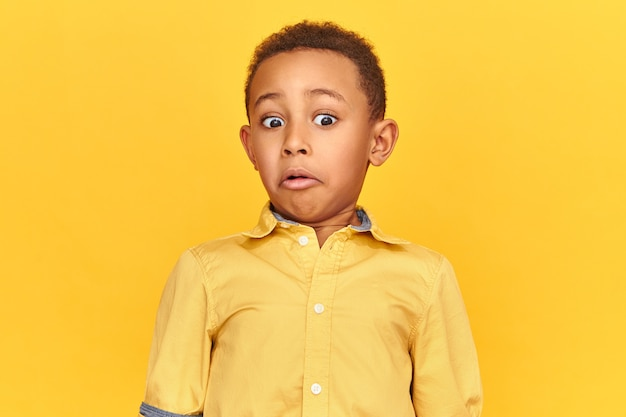 Surprise, astonishment and shock concept. isolated image of shocked astonished african american little boy expressing true surprised reaction, grimacing while looking at something disgusting