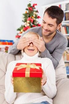 놀라다! 아름다운 젊은 여성이 소파에 앉아 선물 상자를 들고 있는 동안 남자친구는 뒤에 서서 손으로 눈을 가리고 있습니다