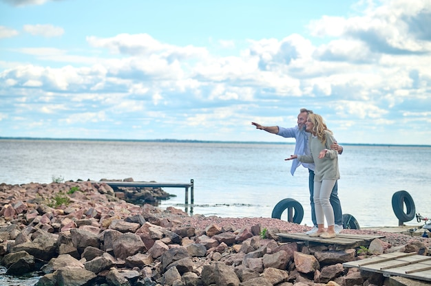 놀람, 기쁨. 손을 뻗은 놀란 즐거운 성숙한 남자와 바다 근처에 서 있는 관심을 갖고 바라보는 여자