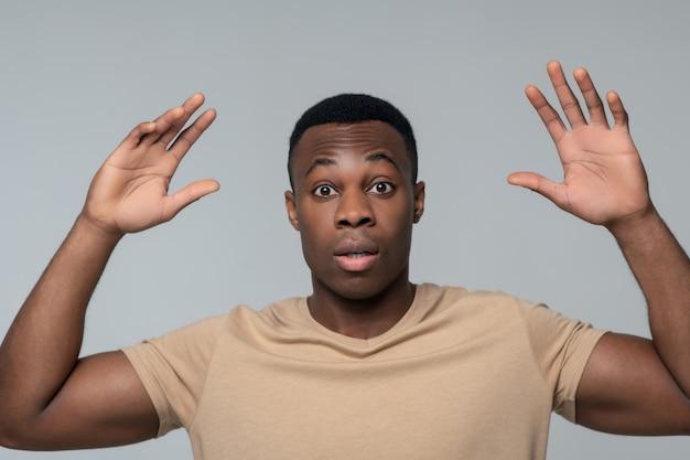 Surprise, disbelief. surprised young dark skinned man with arms raised up standing distrustful gesturing
