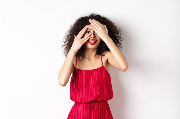 Сюрприз. возбужденная симпатичная девушка с вьющимися волосами и красными губами, выглядывающая сквозь пальцы и изумленно улыбаясь, просматривает промо, стоя на белом фоне.