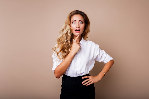Surprise face. blond woman in casual outfit standing over beige wall. exited girl looking.