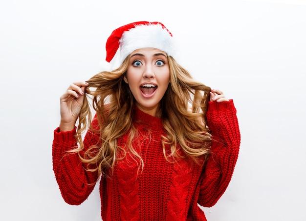 驚きの顔。赤い仮面舞踏会の新年の帽子とセーターの恍惚とした女性