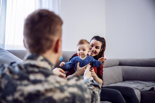 家族のための驚き。勇敢な兵士がついに帰宅した。腕を開いて腕を保持している彼の最愛の息子を抱きしめたい兵士の背面図
