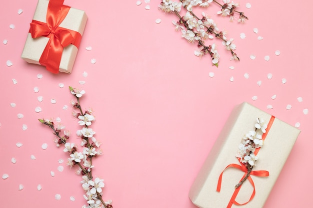 Surprise gift box with a red bow on a pink backgroun