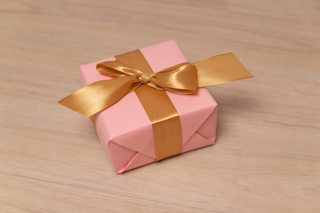 Surprise gift or box wrapped in paper and satin ribbon on a grey background.