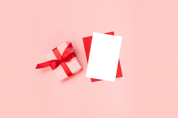 Surprise gift box wrapped in pink paper with a red bow, blank red envelope template on a pink background