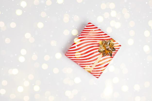 金の弓、モミ、赤い金色のボールが付いたクラフト紙で包まれたサプライズギフトボックス