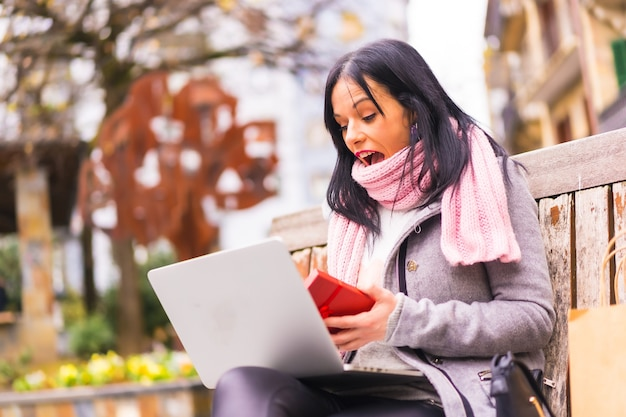 Surprise gift, caucasian brunette girl opening the boyfriend's gift in a video call with the computer, separated by distance