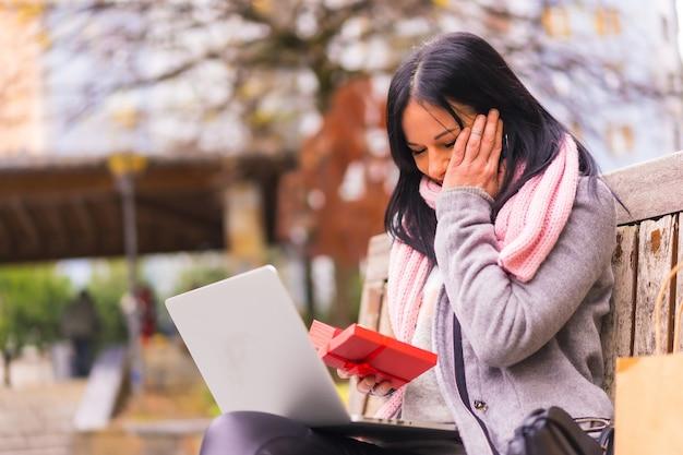 サプライズギフト、距離で区切られたコンピューターとのビデオ通話で彼氏のギフトを開く非常に興奮した女の子