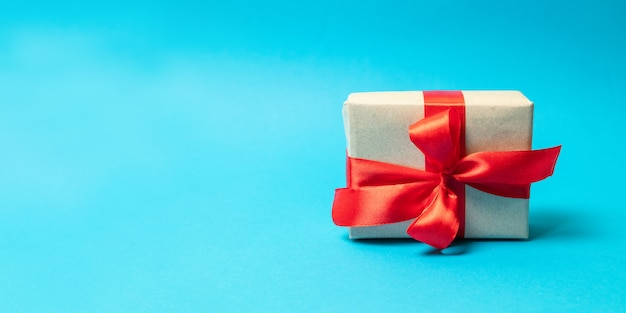 Surprise gift wrap with red ribbon bow on a blue background. happy birthday