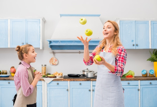 Surprise girl looking at her mother throwing the green apple in air at kitchen