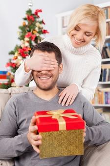 놀라다! 잘생긴 젊은 남자가 소파에 앉아 선물 상자를 들고 있는 동안 여자 친구가 뒤에 서서 손으로 눈을 가리고 있습니다