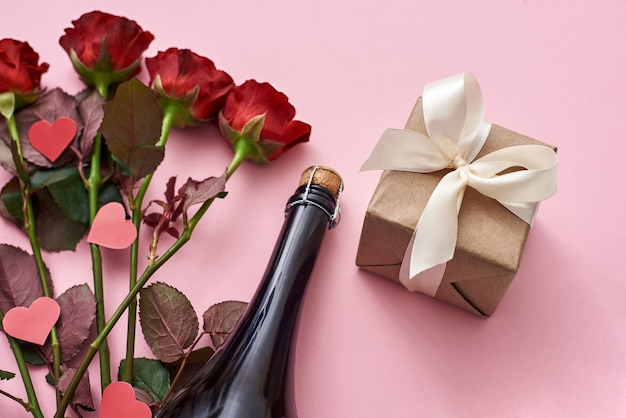 Surprise for her special gift box with white ribbon red roses and champagne