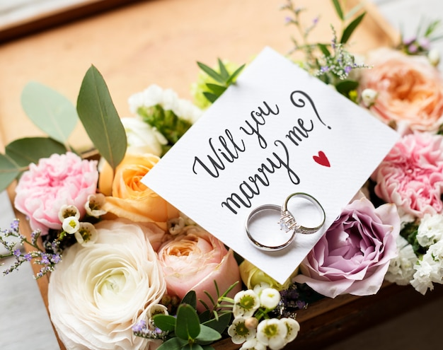 A surprise marriage proposal with will you marry me card and rings