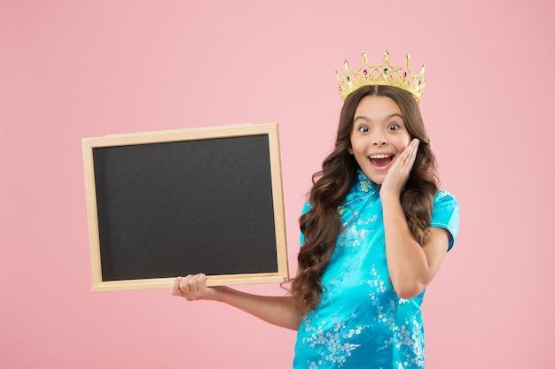 서프라이즈 무도회 밤. 무도회 여왕은 학교 칠판을 들고 있습니다. 작은 아이는 무도회 왕관을 착용합니다. 대관식 파티. 휴일 축하. 자부심과 영광. 명성과 명성. 무도회 정보, 복사 공간.