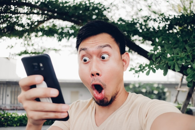 Surprise and shock face of man look at his smartphone.