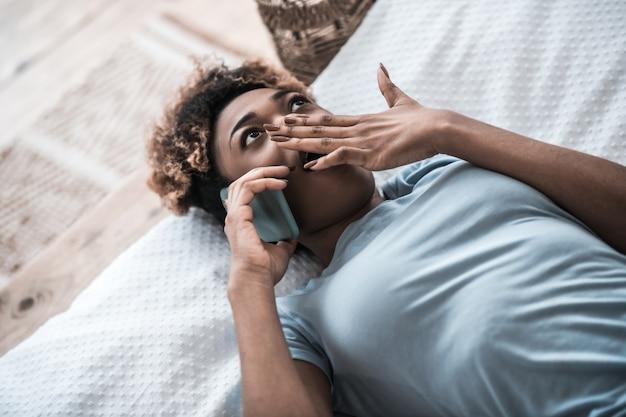 驚き。スマートフォンで手を覆っている驚いた浅黒い肌の女性が自宅のベッドで横になっている口を開けて通信