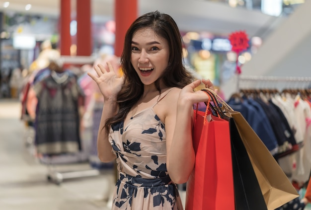 Surprise woman with shopping bags in clothes store