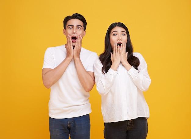놀람 젊은 아시아 커플 남녀가 노란색 배경에 행복하고 놀랐습니다.
