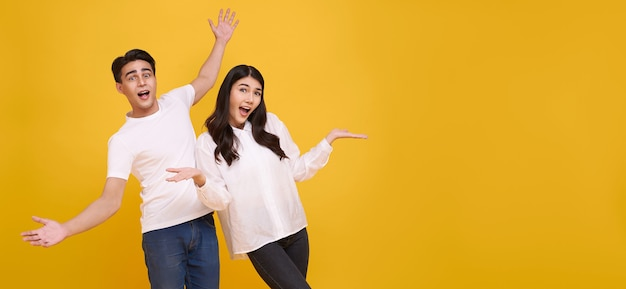 Surprise young asian couple man and woman happy and amazed on panoramic yellow background.