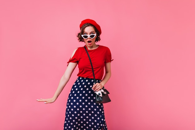 Surprised adorable girl in red beret standing on rosy wall. indoor photo of amazed french lady with wavy hairstyle.