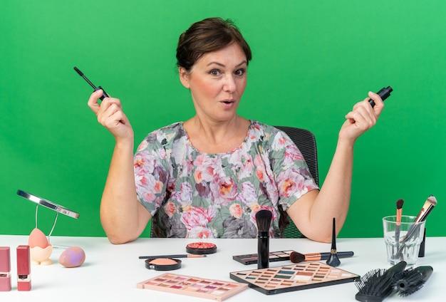 マスカラを保持している化粧ツールとテーブルに座って驚いた大人の白人女性