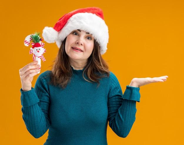 Удивленная взрослая кавказская женщина в новогодней шапке держит конфету и держит руку открытой изолированной на оранжевом фоне с копией пространства