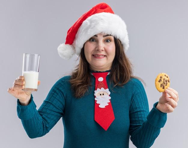 Donna caucasica adulta sorpresa con cappello santa e cravatta santa tenendo un bicchiere di latte e biscotto isolato su sfondo bianco con spazio di copia