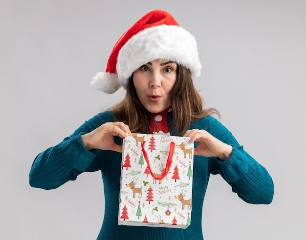 Donna caucasica adulta sorpresa con cappello da babbo natale e cravatta di babbo natale che tiene in mano una scatola regalo di carta isolata sul muro bianco con spazio di copia