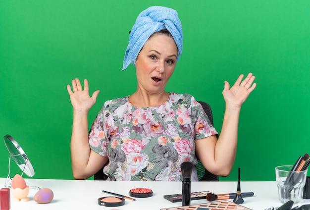 Удивленная взрослая кавказская женщина с обернутыми волосами в полотенце сидит за столом с инструментами для макияжа, держа руки открытыми