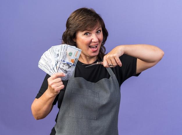 복사 공간이 있는 보라색 벽에 격리된 돈과 가위를 들고 제복을 입은 놀란 성인 여성 이발사