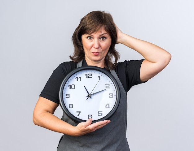 Sorpreso femmina adulta barbiere in uniforme mettendo la mano sulla testa e tenendo l'orologio isolato sul muro bianco con copia spazio