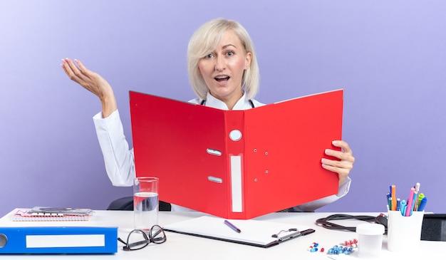 의료 가운을 입은 성인 여성 의사가 청진기를 들고 책상에 앉아 복사 공간이 있는 보라색 벽에 격리된 파일 폴더를 들고 있는 사무실 도구를 들고 놀란 성인 여성 의사